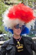 Man with a wig which is coloured like the Dutch flag on Queensday.