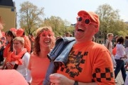 Orange couple laughing on a sunny day during the celebration of Queensday.