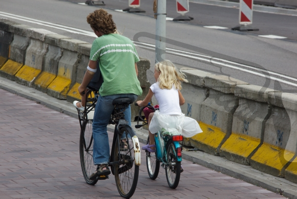 Father and daughter cycling on their way