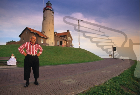 Netherlands, Urk. Senior fisherman in traditional clothing posing in front of a lighthouse. His wife is at the background.