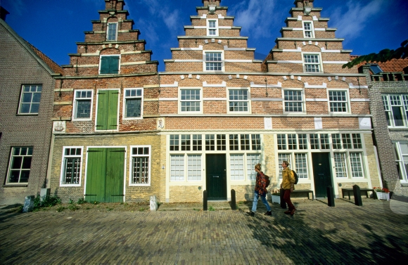 Two people walking in front of stepped gable houses