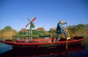 Man in a rowing boat passing a small windmill
