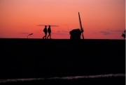 Silhouette of people walking a dyke