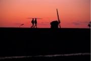 Silhouette of people walking a dyke