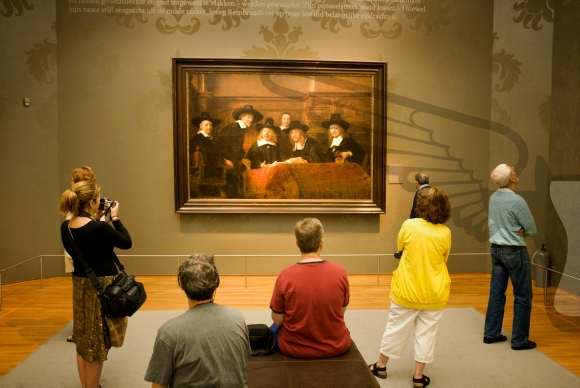 Visitors looking at the painting (The Syndics of the Clothmakers Guild)