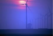 Traditional windmill between modern wind turbines.