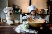Boy is making pancakes while his dog is watching