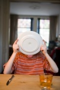Boy licking of his plate while eating dessert