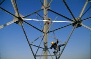 Electricians climbing up a power pylon
